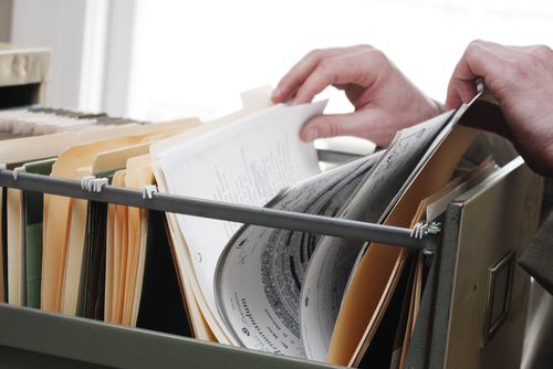hand searching files in cabinet